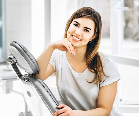Woman in dental chair sharing healthy smile