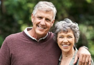 Older man and woman smiling after restorative dentistry