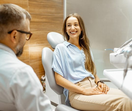 Patient smiling while talking to dentist in treatment chair