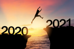 Silhouetted man jumping from cliffs marked 2020 and 2021