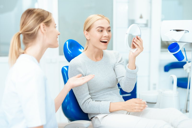 a female patient looking at her new smile in the mirror while listening to her cosmetic dentist