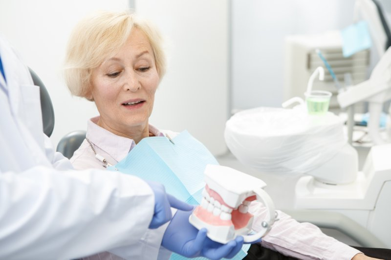 Senior patient looking at a pair of dentures